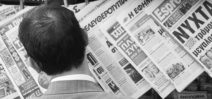 Un griego leyendo el periódico en la calle
