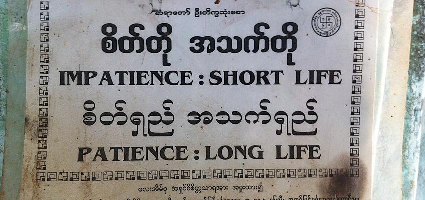 Birmanische Schrift und englische Übersetzung in einem Tempel