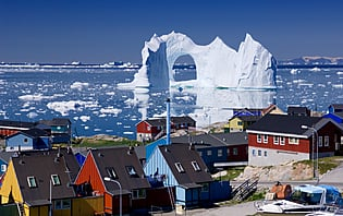 Ice berg of arch and row of houses, Groenland